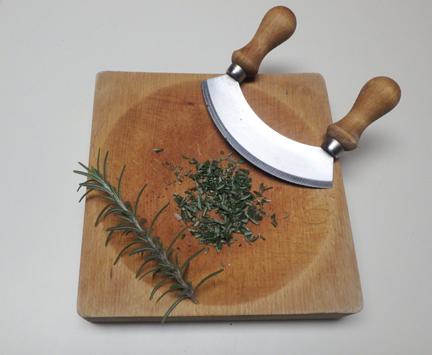 Finely dice fresh rosemary using a sharp knife, such as this mezzaluna and cutting block.